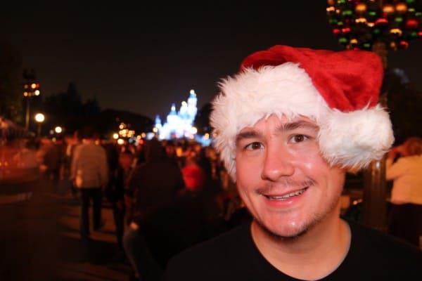 John wearing Mickey Santa Ears in front of Sleeping Beauty's Castle